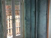 Installation of glass patio doors and cavity drainage membrane to the walls